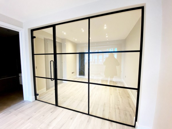 By Developments (Neasden, London): Industrial-Look Office Wall With Black Metal Frame and Toughened Glass